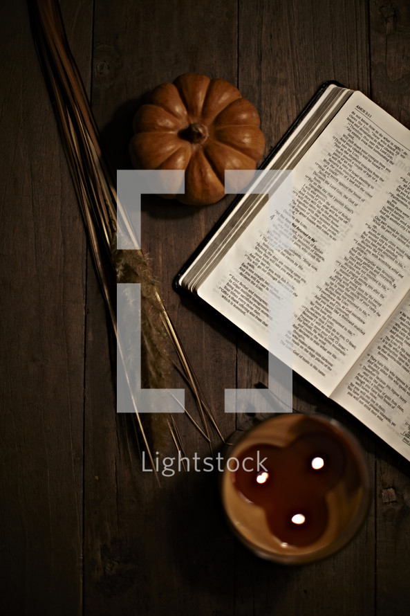 fall scene with bible, candle, and pumpkin