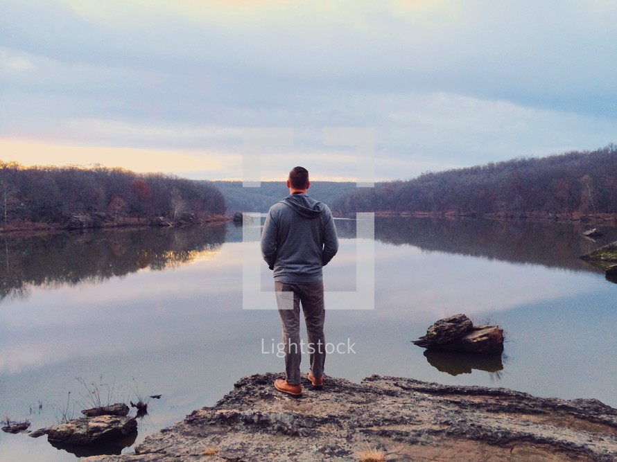 A man standing at a lake shore.