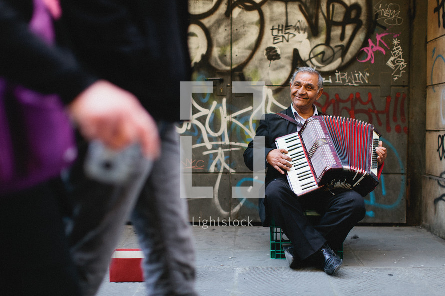 An older man plays the accordion on the street
