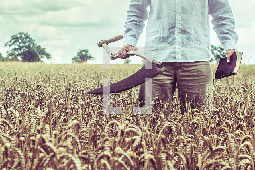 a man with a Scythe blade and a Bible in a wheat field