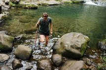 a woman hiking through a stream