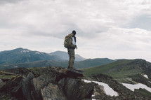man standing on a rocky mountaintop