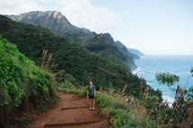 a woman standing on a trail along an island shoreline