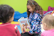a little girl reading a children's Bible