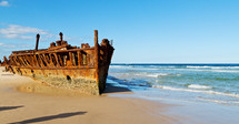 corroded rusty boat on a beach shore