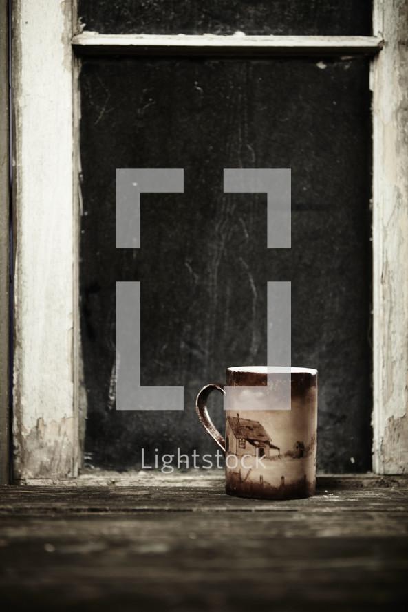 A coffee mug sits next to a window sill