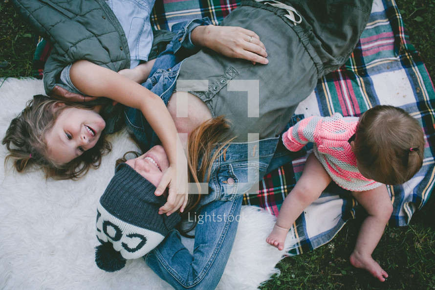a mother and her children lying on a plaid blanket