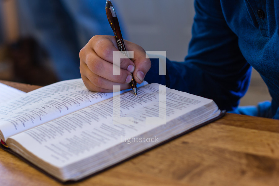 a teen underlining scripture in a Bible