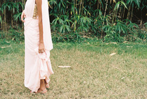 a woman in a long dress standing in grass