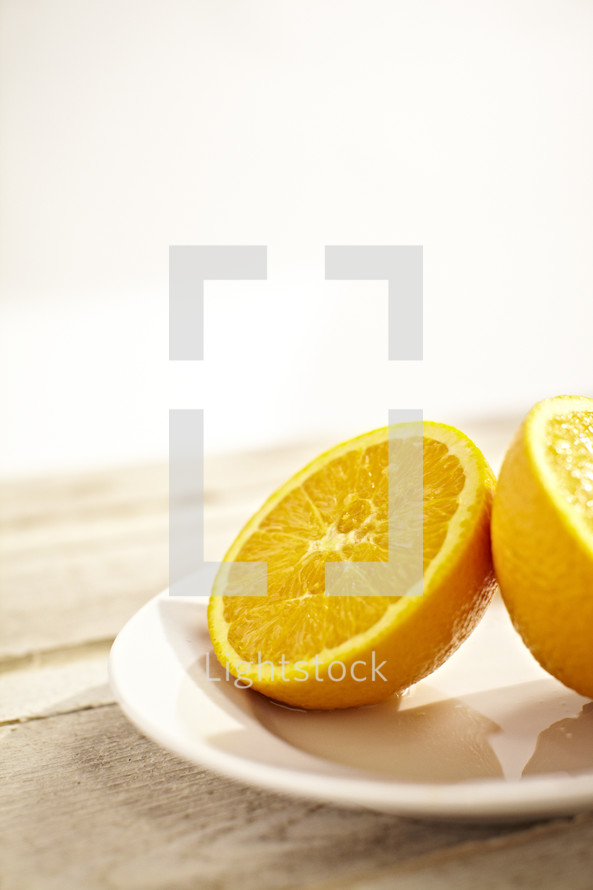 Two halves of an orange on a white plate