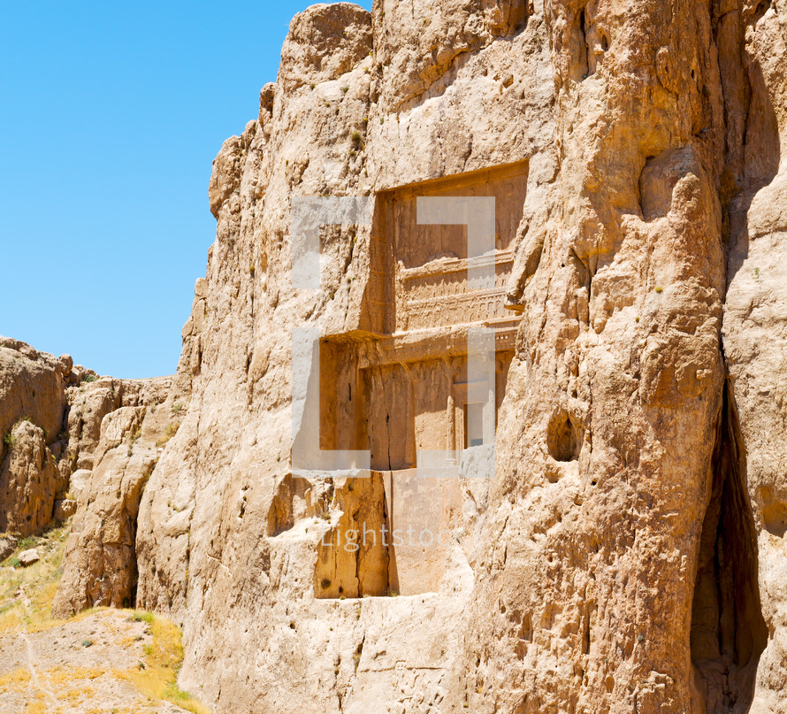 ruins carved into a mountainside in Iran