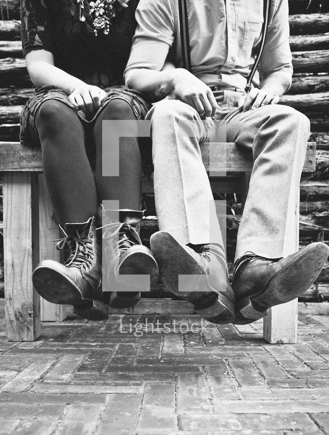 couples legs and feet dangling off a bench