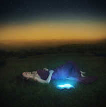 woman lying in the grass and an open Bible glowing