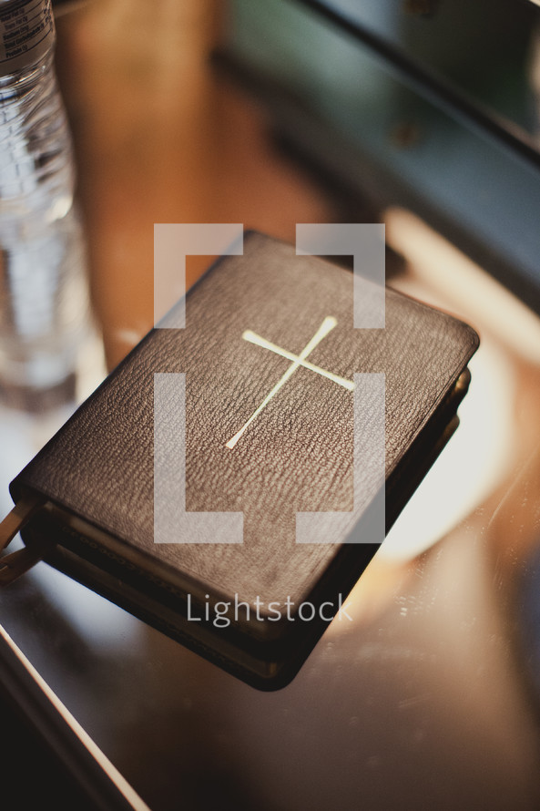 A closed bible with  a large cross on the cover