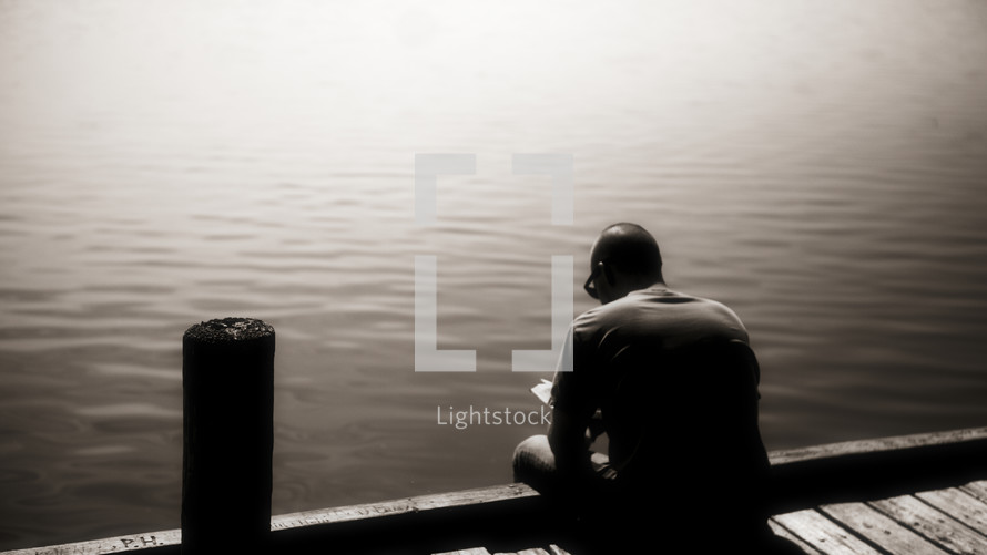 A man reading his Bible on the edge of a dock