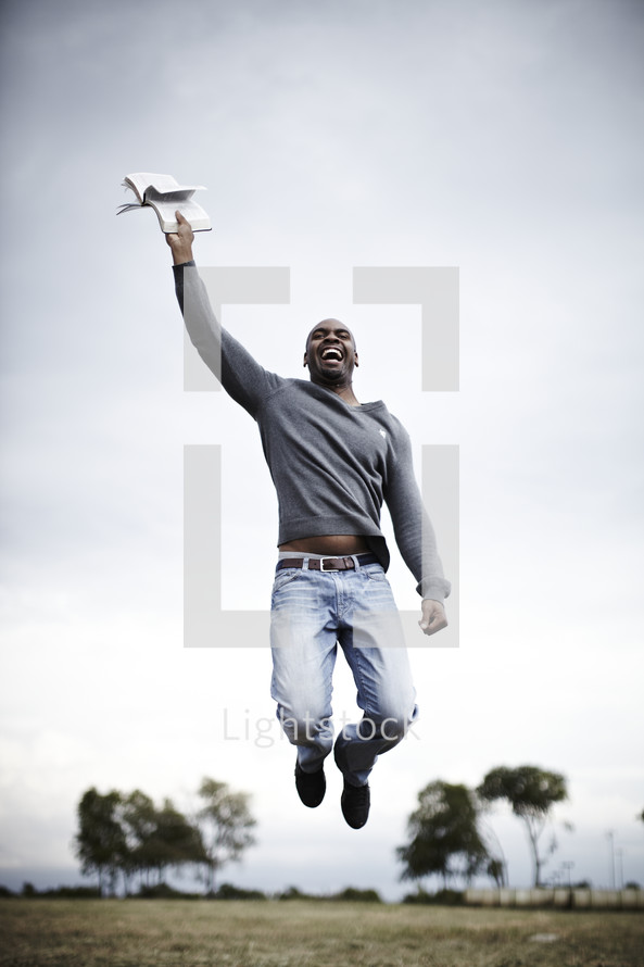 Man jumping in air with bible