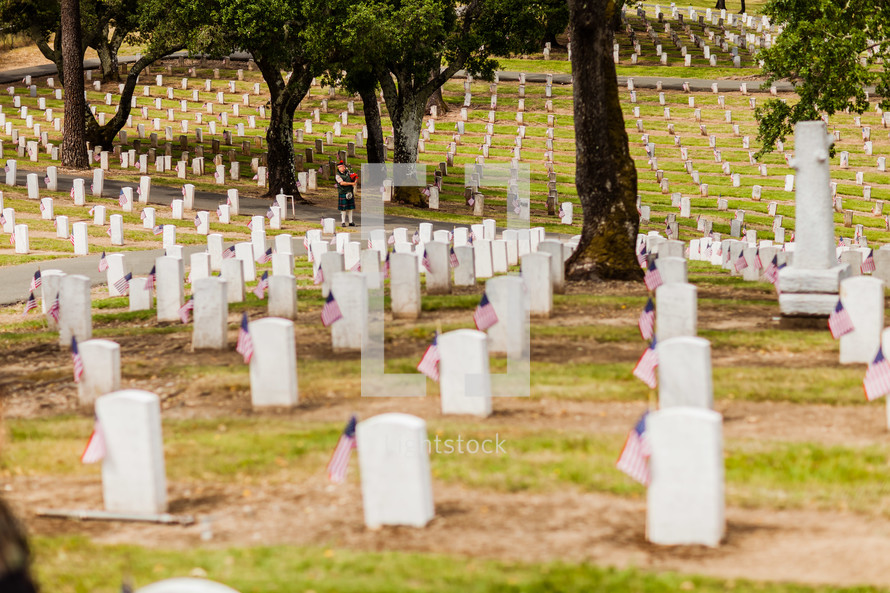 Military graveyard man playing bagpipes burial cemetery tombstone markers American flag 4th of July Independence Day