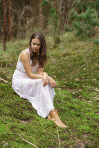 a young woman sitting on mossy ground alone in a forest