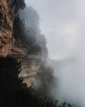 fog in a valley near a mountainside cliff