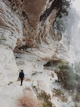 man standing on the edge of a mountainside cliff