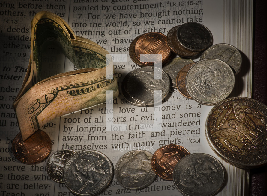 "Paper money heart and coins on Bible pages open to 1 Timothy 6:10 -- ""for the love of money."""