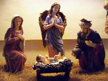A depiction of the Nativity scene  featuring Baby Jesus, Mary, two of the wise men and an angel adoring Jesus at his birth.