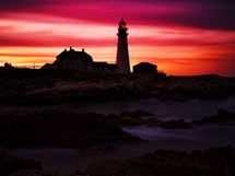 lighthouse at sunset under a red sky