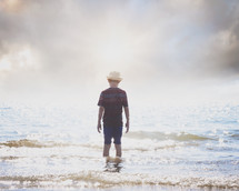 a boy child standing in the ocean