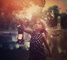 a little girl carrying a lantern with butterflies flying around her