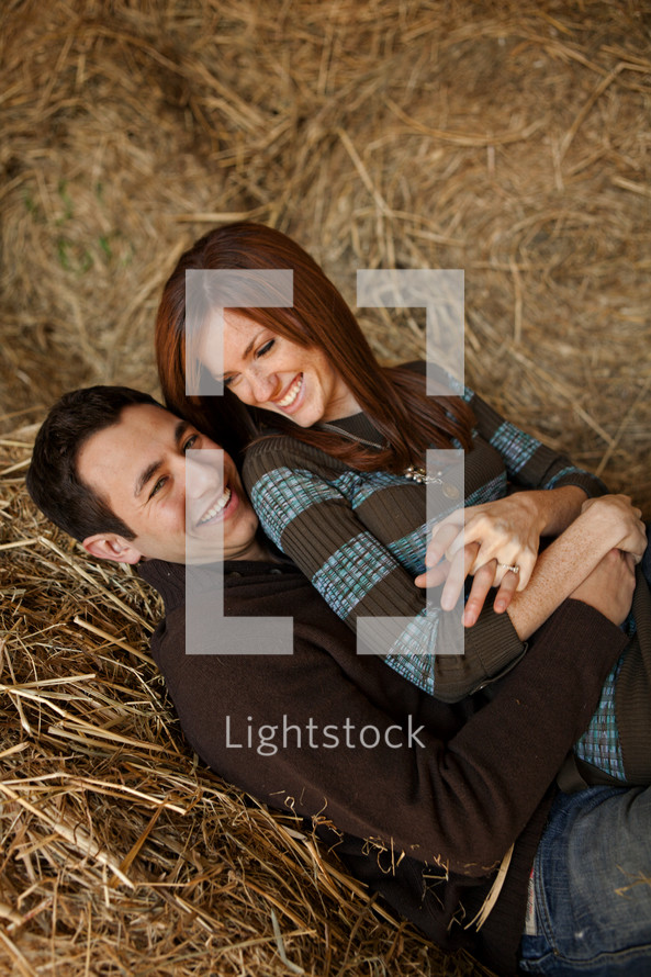 couple snuggling in a hay stack