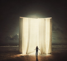 woman standing in front of a giant glowing Bible on a beach