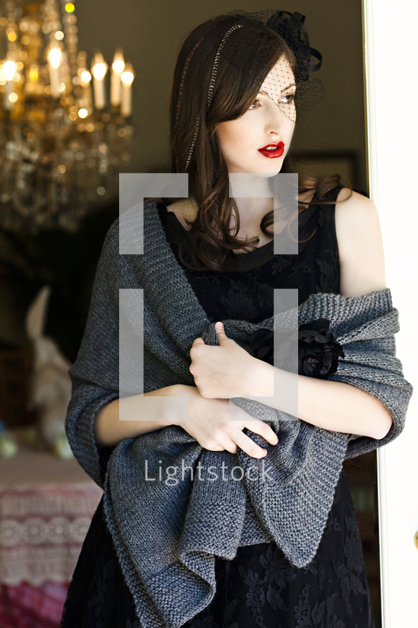 A young woman in a black dress wrapped in a shawl and leaning against a doorjamb vail model fashion