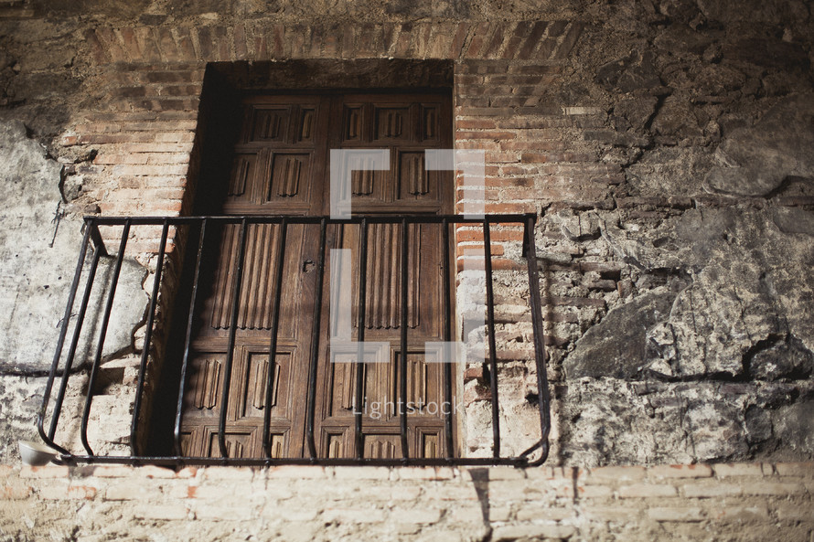 Iron balcony with wooden doors on a brick wall