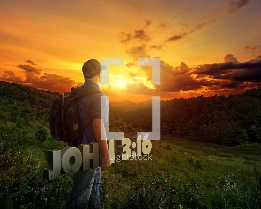 Man in a baseball cap carrying John 3:16 over a hill at sunset.
