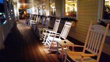 A row of white wooden rocking chairs line a front porch of a local historic inn for summer vacations, retirees and summer renters looking for a restful relaxing vacation.