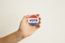 """A hand holding a red white and blue button reading, """"Vote."""""""