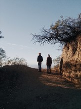 Two men walking on a dirt path.