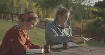 young women sitting outdoors discussing scripture at a fall retreat