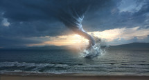 A large tornado on the ocean waters at sunset