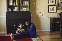 mother and daughter reading together sitting on a rug