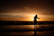 silhouette of a female surfer on a beach at sunset