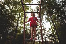a girl child playing on monkey bars