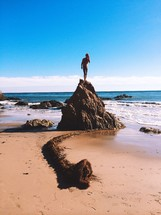 man standing on a rock on a beach