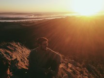 man sitting at the top of a mountain under intense sunlight