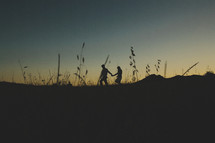 silhouette of a couple walking holding hands in a field at sunset