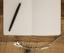 pen on an open journal and earbuds