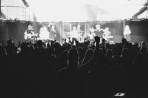 Man praising Jesus from the back row during worship.