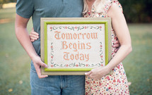 couple holding a framed picture - Tomorrow Begins Today