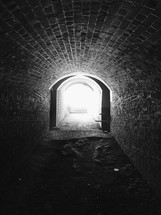 Bright light at the end of a stone tunnel.