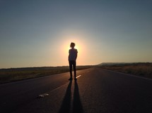 man standing in the center of a road